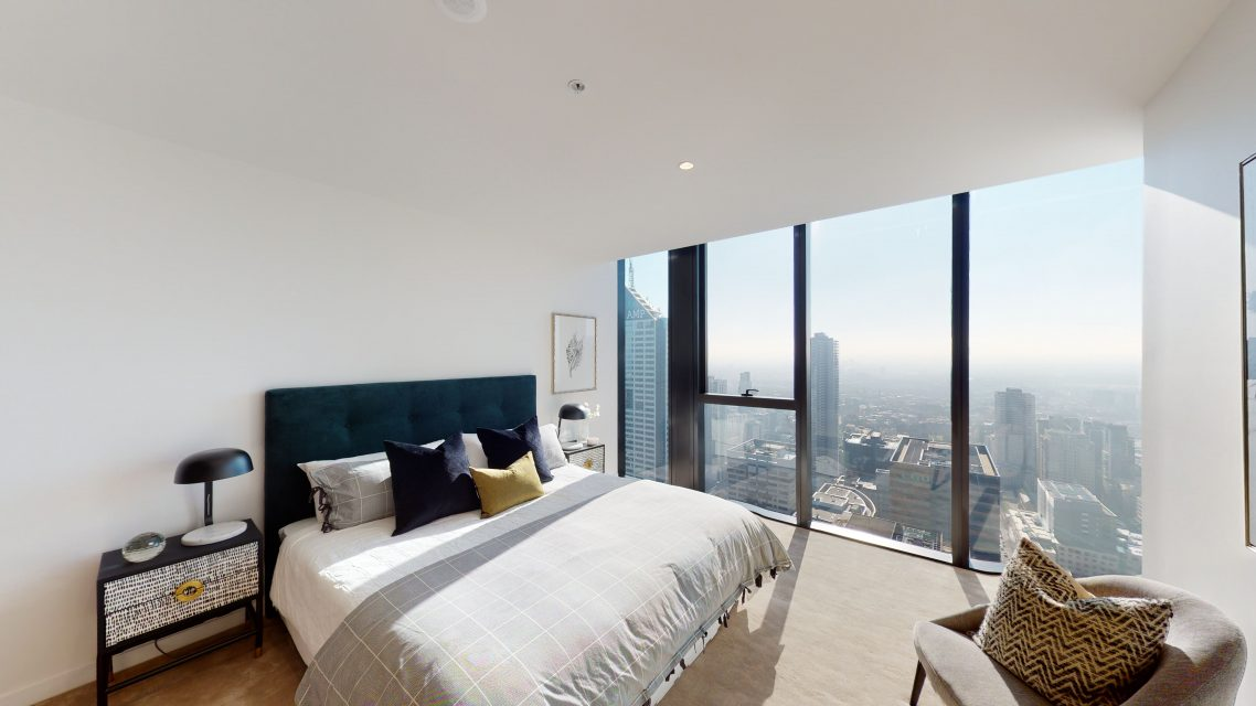 Bedroom with large windows and city views