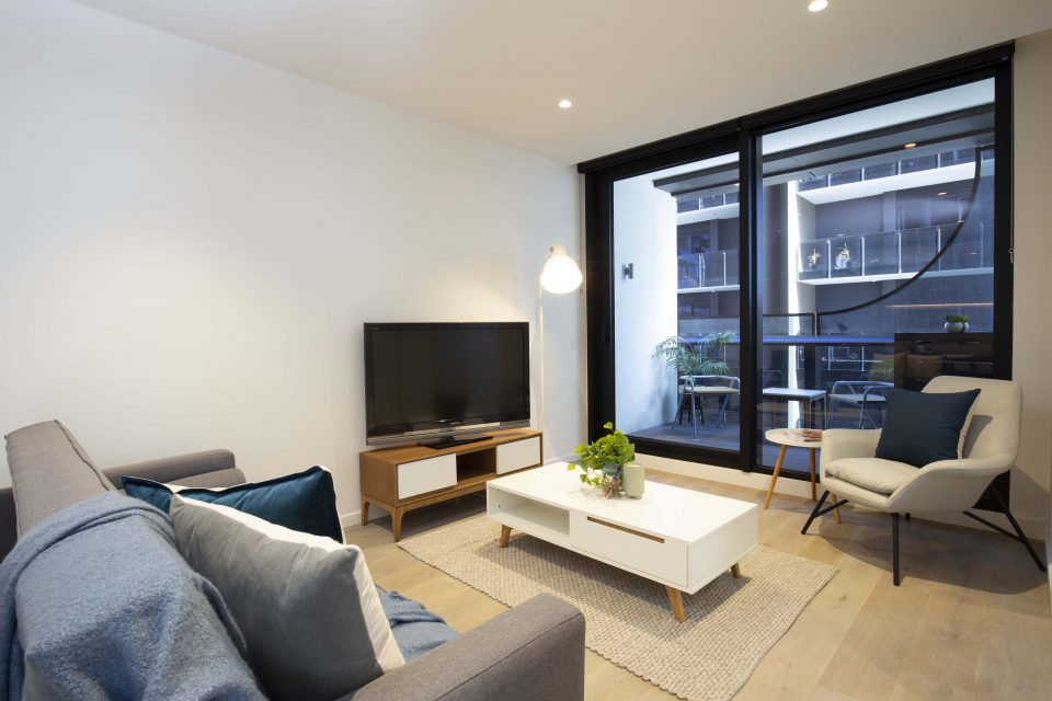 Living area with coffee table, television and balcony access