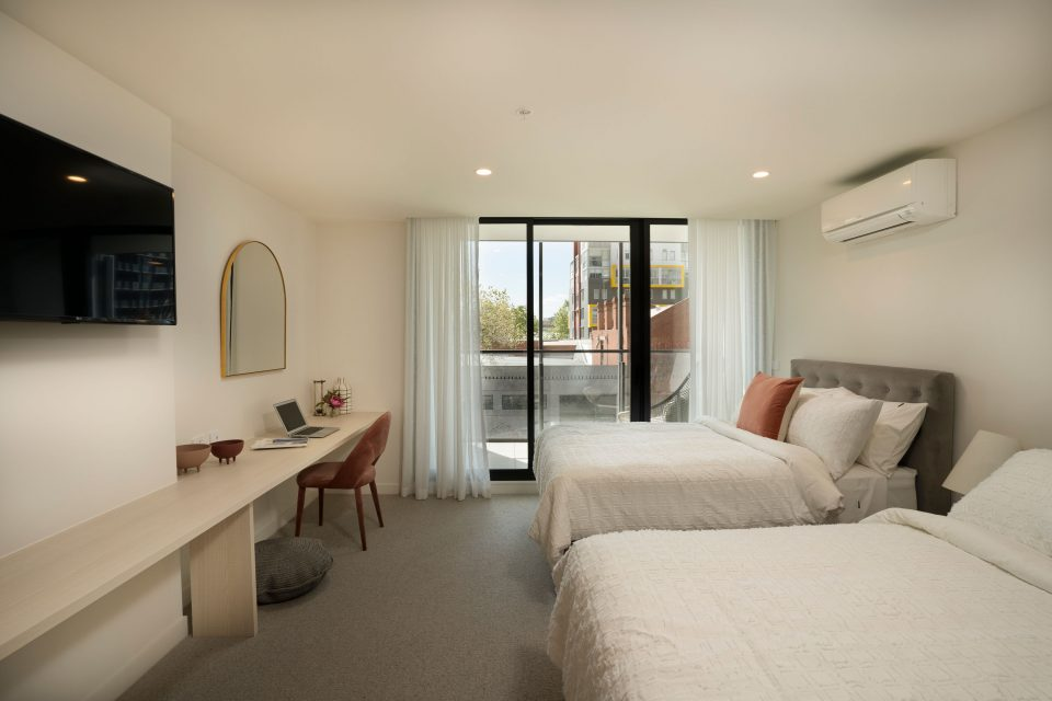Two beds side by side with balcony access