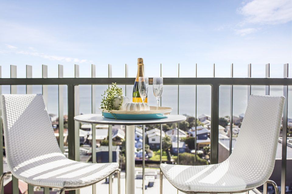 Outdoor balcony with table chairs and champagne